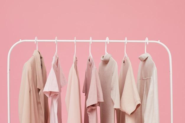 ピンクの背景で隔離のラックにぶら下がっている服