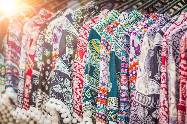 Clothes hanging on a rack in a flea market souvenir shop in thailand