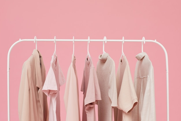 Clothes hanging on the rack isolated on pink background