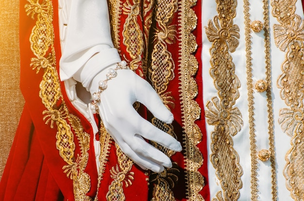 Clothes of a historical imperial woman with red elements, a hand in white gloves.