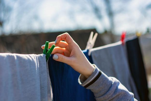 Одежда прицепленная прищепками весит на веревке