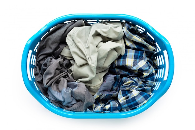 Одежда в голубой пластиковой корзине для белья на белом фоне.