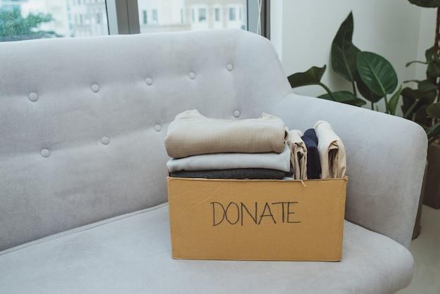 コンセプトの寄付と再利用のリサイクルのための箱の中の服