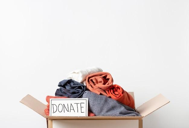 Одежда в картонной коробке и надпись пожертвовать на белом, копией пространства