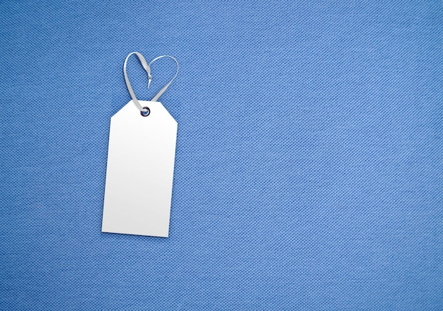 Clothes label tag on cloth background. branding template mockup. color of the year 2020 classic blue