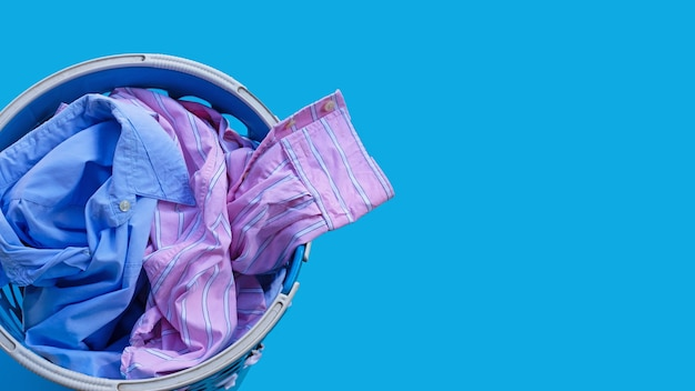 Clothes in a laundry basket on blue. copy space