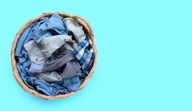 Clothes in laundry basket on blue wall.