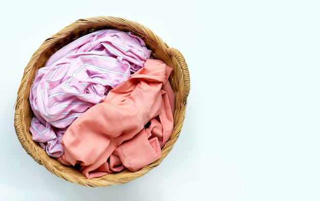 Clothes in laundry basket on white surface. copy space