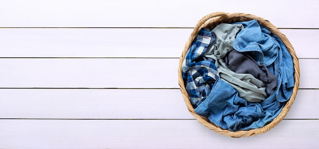 Clothes in laundry basket on white wooden background.