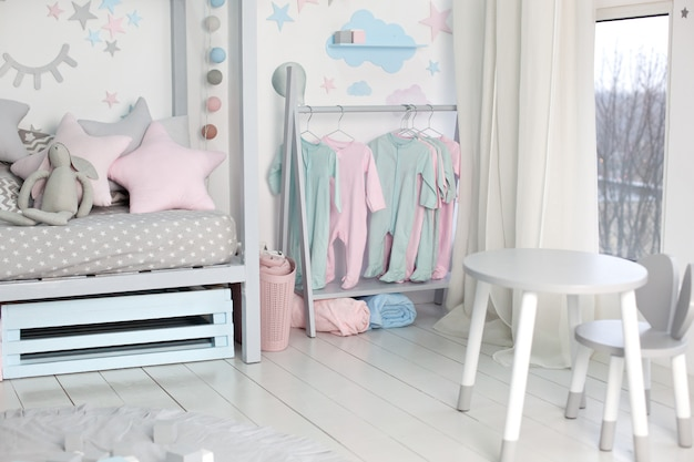 Clothes for little child hung in children room. rack with hangers with baby clothes. children cloth rack. pastel color children clothes in a row on open hanger indoors. children's bedroom.  home decor