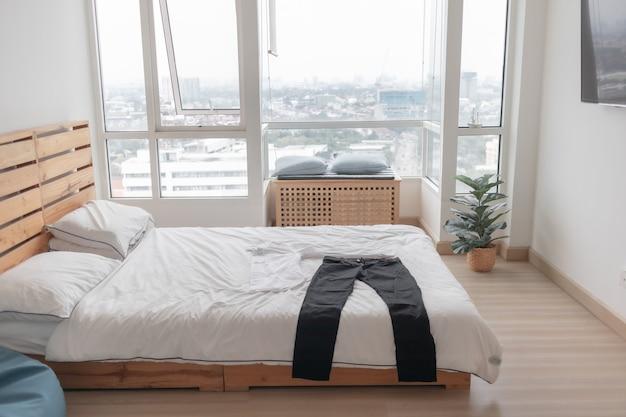 準備の概念で寝室のベッドに横たわっている服