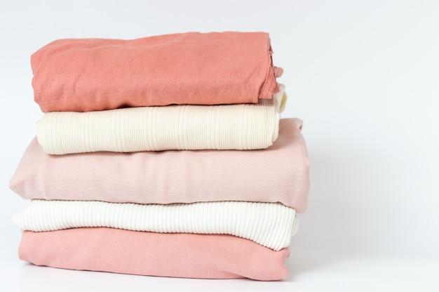 パステル調の色合いの服が白い背景のスタックにきれいに折りたたまれています