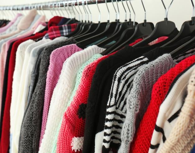 Одежда на вешалках в современном магазине, крупным планом