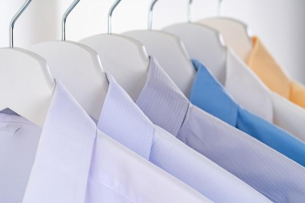 Одежда на вешалках на белом фоне