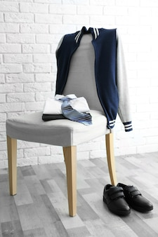 Clothes of schoolboy on chair indoors