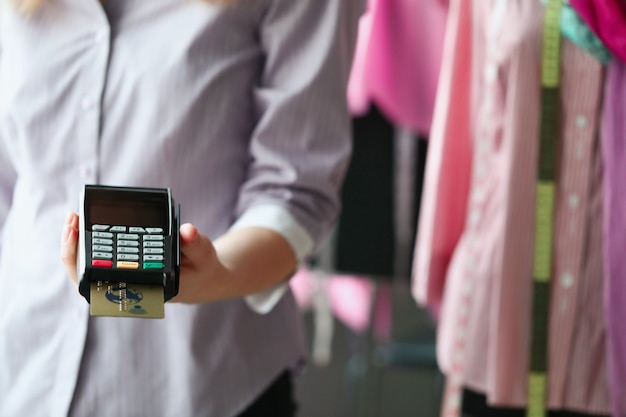 Clothes seller holding pos terminal in his hands in shop closeup