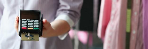 상점 근접 촬영에서 그의 손에 pos 터미널을 들고 옷 판매자