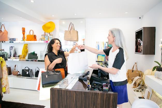 Кассир магазина одежды дает бумажный пакет покупателю над столом с кассовым аппаратом. вид сбоку. шоппинг или концепция потребительства