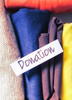 Сортировка одежды в домашнем шкафу для вертикального хранения для пожертвования с бумажной запиской на мягком розовом фоне.