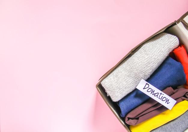紙幣で寄付するための家庭用ワードローブ垂直保管庫での衣類の仕分け