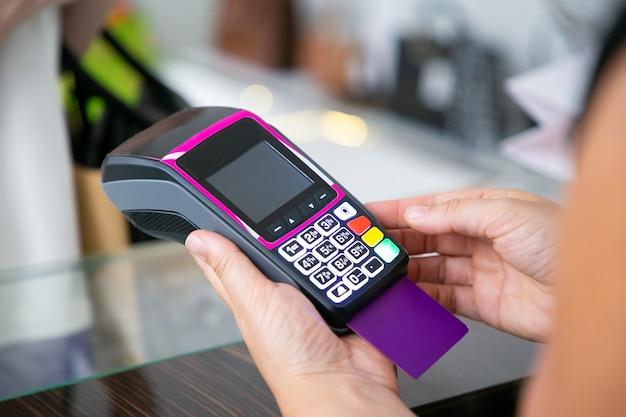 衣料品店のレジ係は、pos端末とクレジットカードを使用して支払いプロセスを操作します。クロップドショット、手のクローズアップ。ショッピングや購入のコンセプト