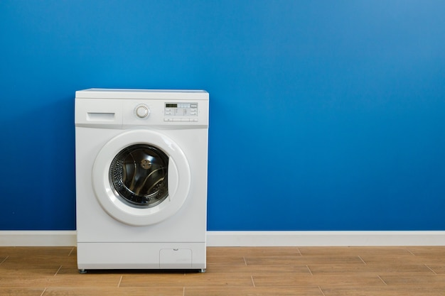 Clothes washing machine in laundry room interior on blue wall, copy space