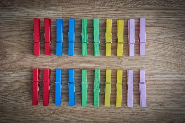 木製の背景にカラフルな木製のclothespin。第2の行に配置される。規則性のアイデアとコンシューマ
