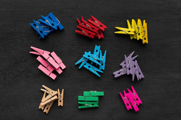 Прищепки разных цветов делятся на группы. наборы ярких прищепок на черной поверхности.