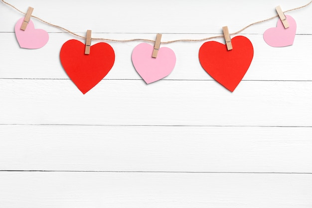 Clothespins with colored hearts hanging on rope behind white wooden surface. copy space, top view.