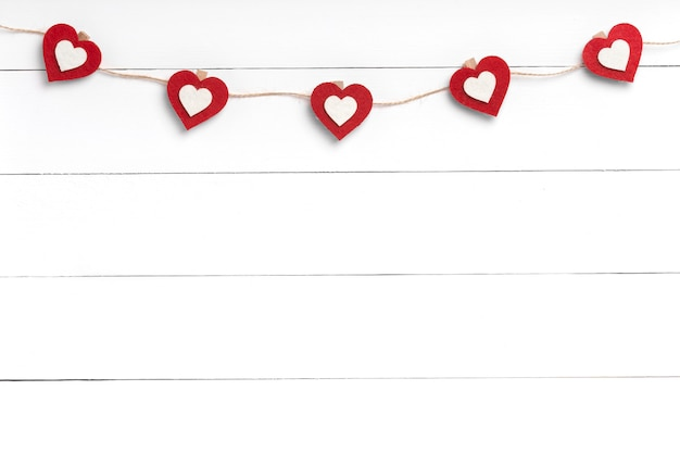 Clothespins with red hearts hanging on string behind white wooden surface. copy space, top view.