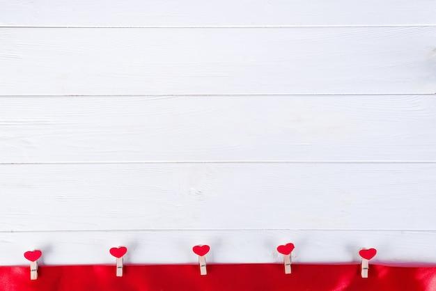 Прищепки с красными сердечками на красной ленточке на белом деревянном фоне дня святого валентина