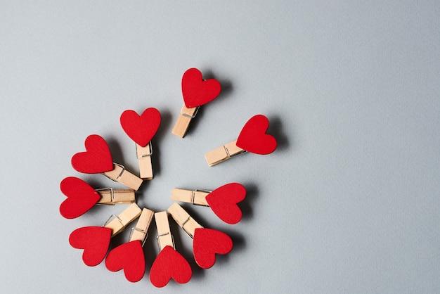 Прищепки с деревянными сердечками в конце на сером фоне день святого валентина праздничное украшение. фото высокого качества