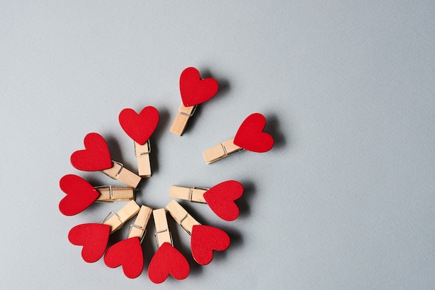 Clothespins with wooden hearts at the end on a gray background valentine's day holidays decoration. high quality photo