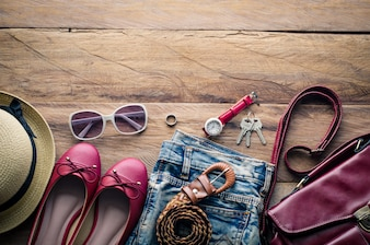 Clothing and accesories for women, placed on a wooden floor.