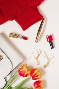 Одежда и косметика блогера и букет тюльпанов. скопируйте пространство. вид сверху
