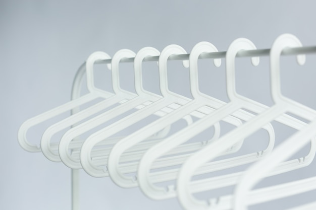 Clothing, costume and accessories concept - plastic hangers on a rod on white wall