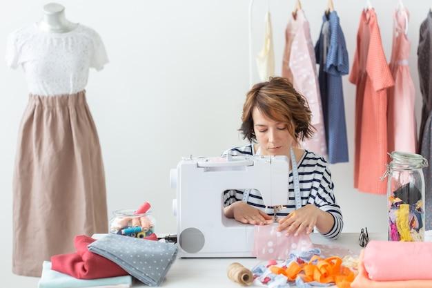 Дизайнер одежды, швея, люди концепции - женщина-швея работает в своей студии