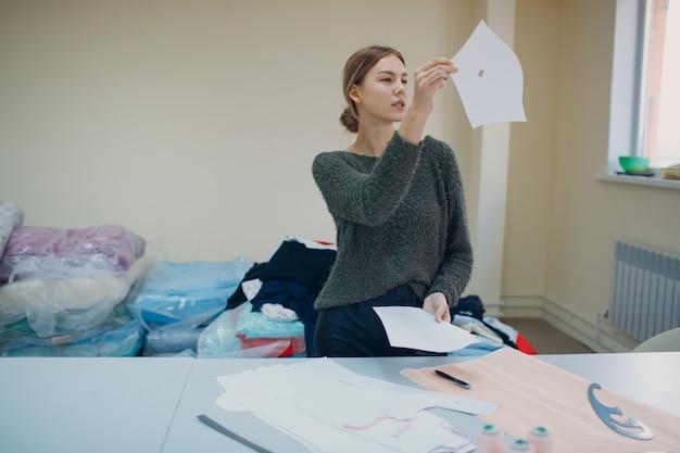 布地工場でパターンとテンプレートを持つ衣料品デザイナー