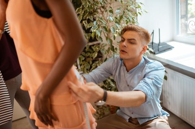 服の詳細。スタジオのモデルに新しいオレンジ色のドレスを合わせる金髪の若いファッションデザイナー
