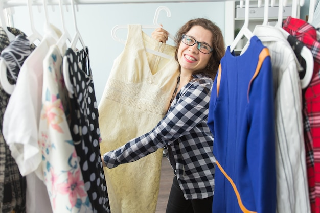 服、ファッション、スタイル、人々の概念-女性の自宅のワードローブで服を選ぶ