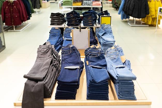 다양한 종류의 바지와 청바지가 옷걸이에 걸려있는 옷가게