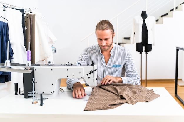 Стилист по одежде создает новый дизайн платья - модельер работает над брендом одежды на текстильной фабрике.