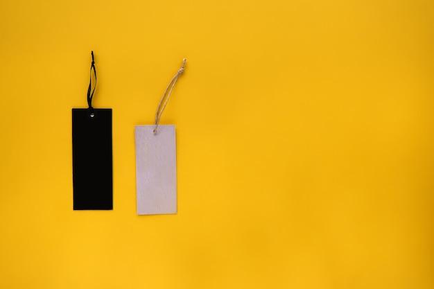 服のタグ、ラベルの空白のモックアップテンプレート、黄色の紙の背景に分離されたデザインを配置します。