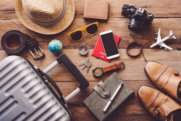 旅行の準備ができている荷物の中の木製の床にある旅行者のパスポート、財布、眼鏡、スマートフォンデバイスの衣類。