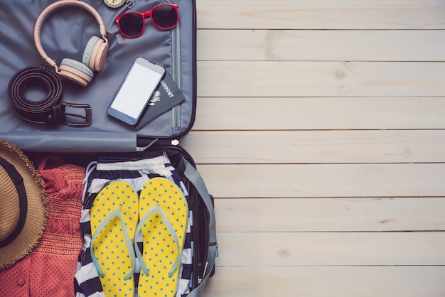 Clothing traveler's passport, wallet, glasses, smart phone devices, on a wooden floor