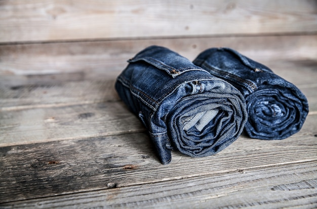 Одежда. скрученные джинсы на деревянном столе