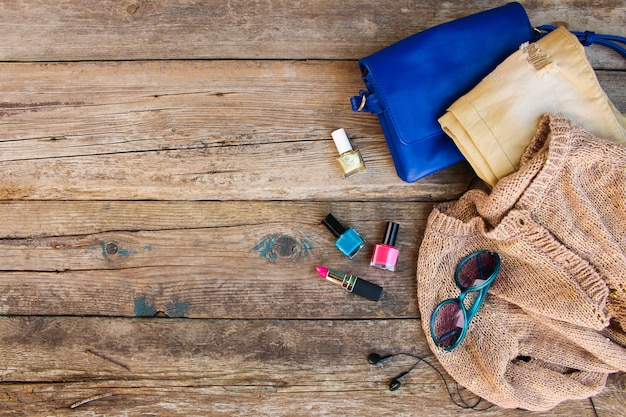 Clothing, women's accessories and cosmetics on old wooden background