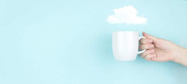 클라우드 컴퓨팅 개념입니다. 여자 손은 파란색 배경에 추상 구름 기호 아이콘이 있는 모닝 커피 컵을 잡고 있습니다. 추상 클라우드 연결 기술 배경입니다.