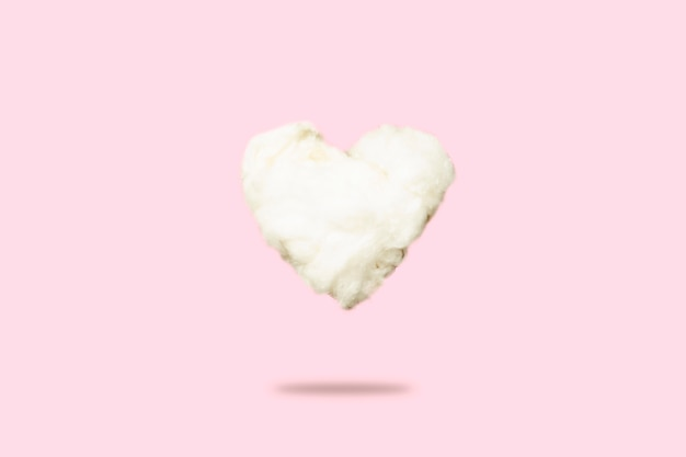 Cloud of cotton wool in the shape of a heart on a pink. love concept, valentine's day.
