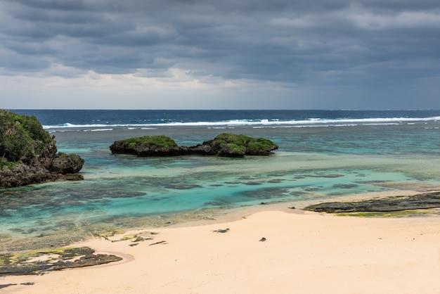 星砂の浜の雲の日灰色の雲が偏光したターコイズブルーの海のサンゴ礁西表島